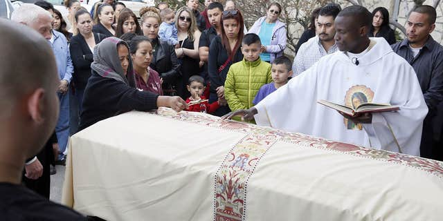 Feb. 25, 2015: Agapita Montes-Rivera, left, places a crucifix on the coffin of her son, Antonio Zambrano-Montes during his funeral service conducted by Rev. Lutakome Nsubuga.