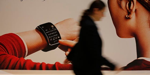 File photo. A visitor walks past a billboard advertising Samsung Gear S smartwatch at the IFA consumer technology fair in Berlin, September 5, 2014.
