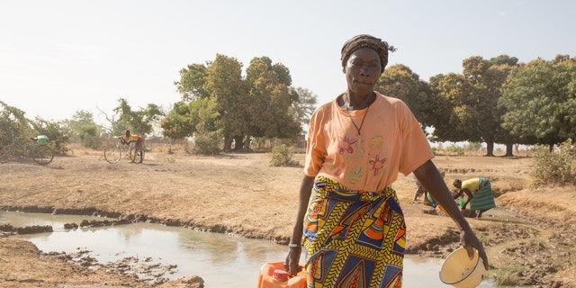 Odette Sompougdo, standing near the dregs of a stream, holding a jerrycan and a dish to collect water from the holes dug around, Vy district in Nassoulou Village, Burkina Faso, January 2016.