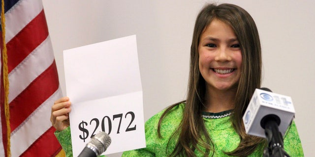 FILE 2015: Student Shania Sommer of Palmer, Alaska, announces that nearly every Alaskan will receive $2,072 from the year's oil dividend check during a news conference in Anchorage, Alaska.