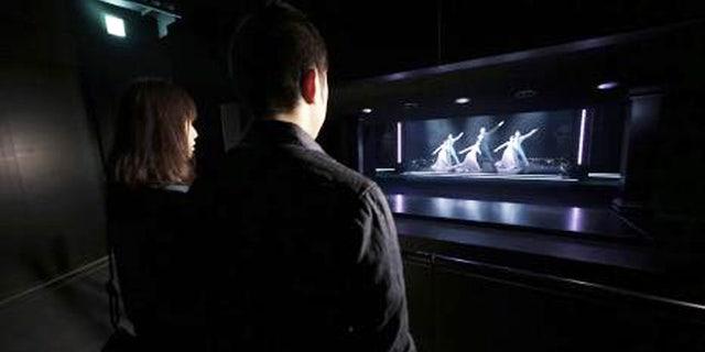 Museum visitors admire the digital dancers.