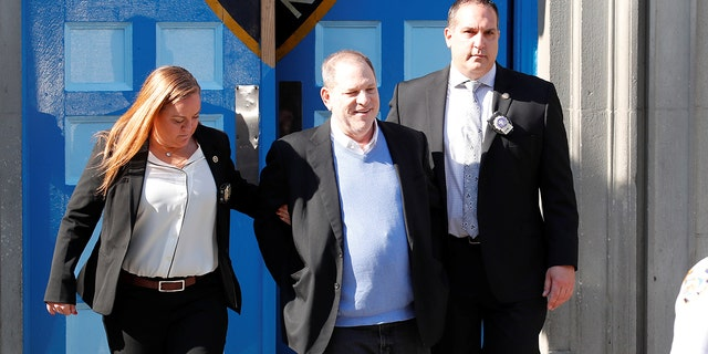 Harvey Weinstein smiled as two officials escort him, handcuffed, to a car after he was charged with rape, criminal sex act, sex abuse and sexual misconduct in incidents on two separate women.