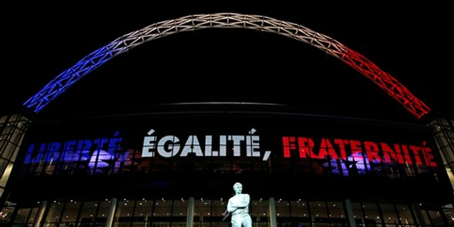 The statue of England soccer legend Bobby Moore stands out side a Wembley Stadium that bears the French nationals colours before the international friendly soccer match between England and France in London,  Tuesday, Nov. 17, 2015. France is playing England at Wembley on Tuesday after the countries decided the match should go ahead despite the deadly attacks in Paris last Friday night which killed scores of people. (AP Photo/Alastair Grant)