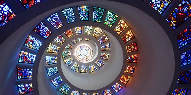 EYY684 Low angle view of spiraling stained glass windows in church