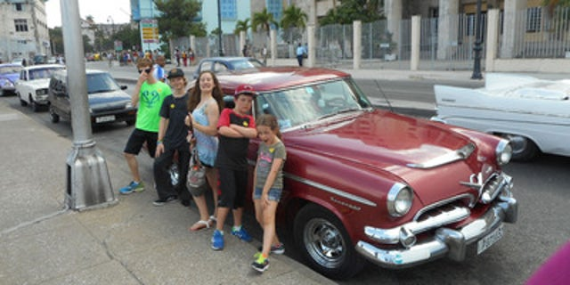 Kids from Adonia mugging for camera in front of vintage '50s-era American car in Old Havana.