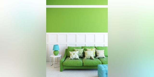 green sofa in green room with lamp