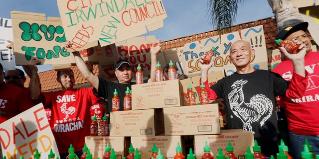 Sriracha hot sauce founder David Tran, second from right, with his workers and supporters protest ahead of the city council meeting in Irwindale, Calif., Wednesday, April 23, 2014. The Irwindale City Council has declared that the factory that produces the popular Sriracha hot sauce is a public nuisance. (AP Photo/Damian Dovarganes)