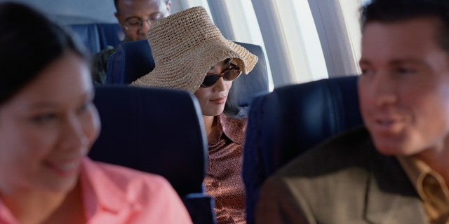 Young woman relaxing on airplane with hat and sunglasses