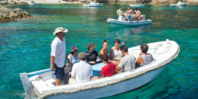 VIS, CROATIA - AUGUST 20, 2012: Tourists on boat to the Blue Hole cave.