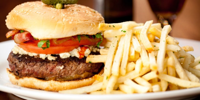 Bacon Cheeseburger with french fries served in restaurant