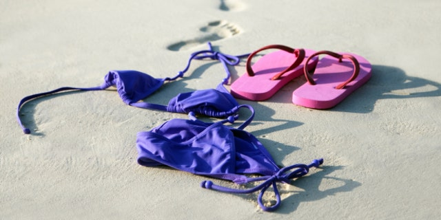 nude woman walking away from her bikini and flip-flops going toward the water