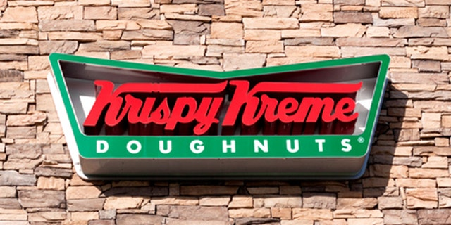 Chula Vista, USA - April 29, 2011: Red and green Krispy Kreme Doughnuts Sign as viewed from the sidewalk.  The building exterior is made of stone with blue awnings for each store window.  Krispy Kreme Doughnuts have been in business serving doughnuts and coffee since 1937.  Krispy Kreme Doughnut stores operate in 14 countries around the globe.