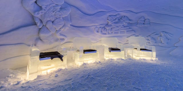 D48JJ0 Interior of the Kirkenes Snowhotel, Norway, showing furniture made from ice and snow sculptures on the wall