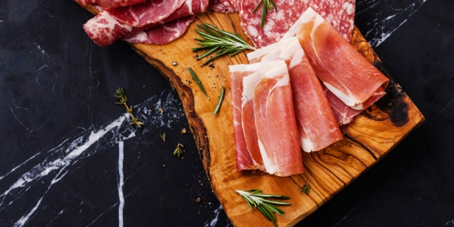Sliced prosciutto di Parma on wooden board with salami and rosemary on black marble background