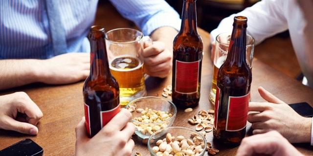 Menâs hands holding beer and pistachio