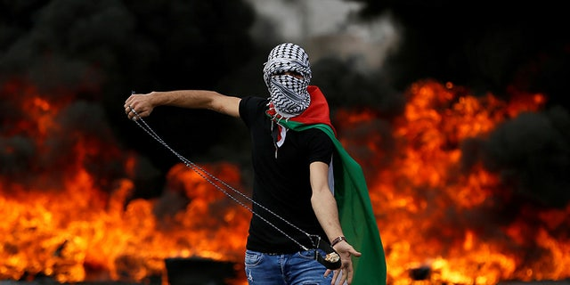 May 15, 2018: A Palestinian demonstrator holds a sling during a protest marking the 70th anniversary of Nakba, near the Jewish settlement of Beit El, near Ramallah, in the occupied West Bank.