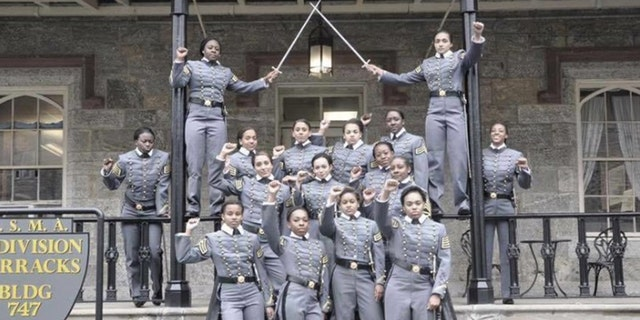FILE- This undated file image obtained from Twitter on Saturday, May 7, 2016 shows 16 black, female cadets in uniform with their fists raised while posing for a photograph at the United States Military Academy at West Point, N.Y.