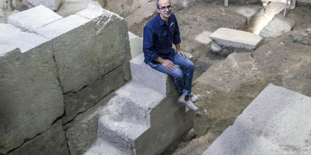 Dr Joe Uziel of the Israel Antiquities Authority, sitting on the steps of the theater structure. (Photograph: Yaniv Berman, courtesy of the Israel Antiquities Authority)