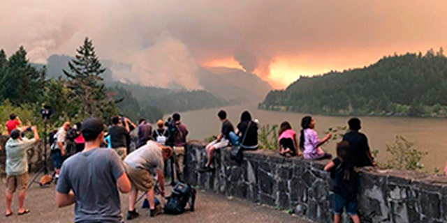People watch the Eagle Creek wildfire burning in the Columbia River Gorge east of Portland, Ore.