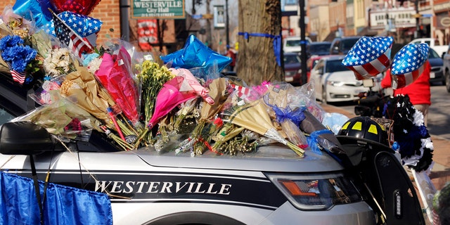 Flowers and signs adorn a Westerville Police car at a memorial outside the police department following a procession transporting the bodies of Westerville Police Officer Eric Joering and Anthony Morelli from the Franklin County Coroners Office to the Hill and Moreland funeral homes in Westerville, Ohio, Monday, Feb. 12, 2018.