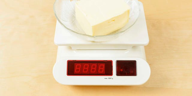 Lump of butter in glass bowl on digital scale.