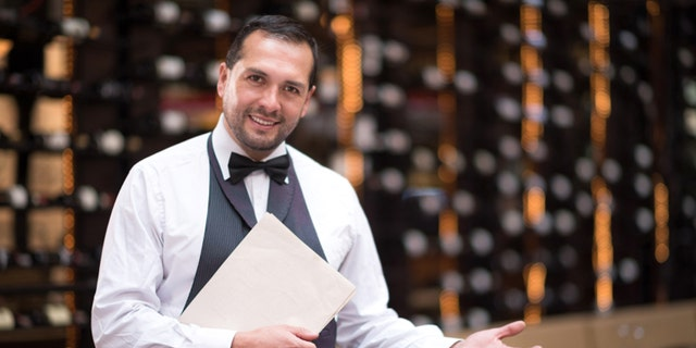 Friendly elegant waiter welcoming people to a restaurant
