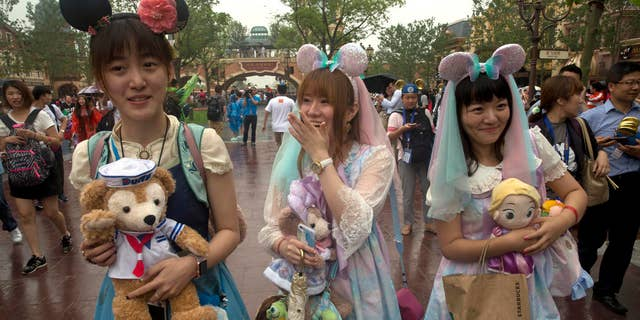 Visitors dress up as they attend the opening day of the Disney Resort in Shanghai, China, Thursday, June 16, 2016.