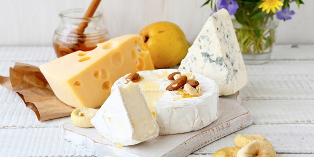 Assorted cheese on a wooden background