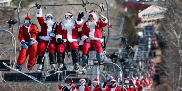 Skiers and snowboarders dressed as Santa ride a chairlift while participating in Santa Sunday at the Sunday River ski resort.
