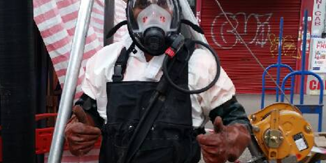 A workman in protective clothing prepares to go into the sewer.