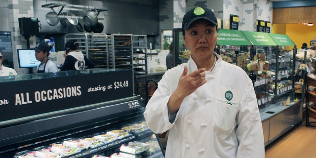 In this April 3, 2018, photo, mountain climber Lhakpa Sherpa prepares to start her shift as a dishwasher at the Whole Foods Market in West Hartford, Conn. Once a year Sherpa heads back to her native Nepal to try and break her own record for successful summits of Mount Everest by a woman.