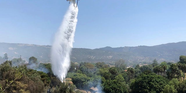 A helicopter drops water in concert with firefighters on the ground trying to extinguish stubborn smoldering areas of the fire off Fairview Ave., in Goleta, Calif.