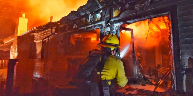 A firefighter puts water on flames at a home off Fairview Ave., in Goleta, Calif.