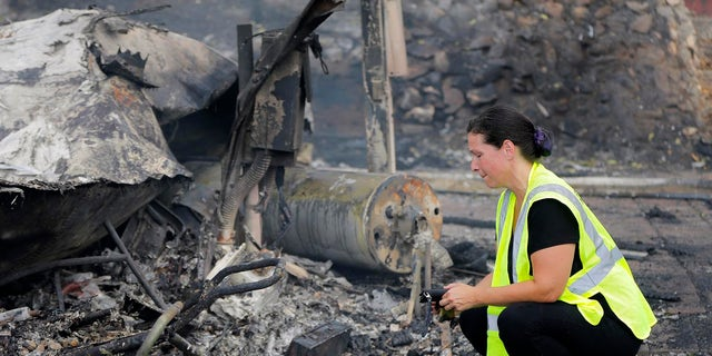 A woman looks at the charred remains of her mobile home after it was destroyed by a wildfire in the Alpine Oaks Estates where she has lived for more than eight years, in Alpine, Calif., Saturday, July 7, 2018.