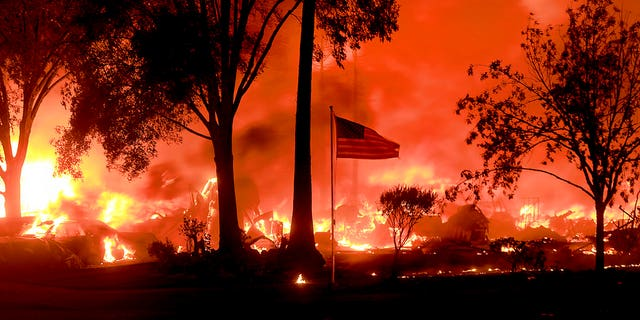 An American flag flies as structures burn in Coffey Park on Monday.