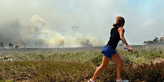 Apr. 30, 2014: A resident talks on her phone as she watches the Etiwanda Fire in Rancho Cucamonga, Calif.