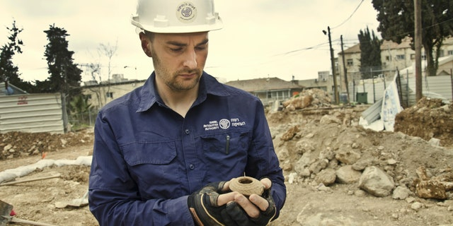 Excavation director, Alex Wiegmann, holding an oil lamp from the Late Roman period that was found at the site.