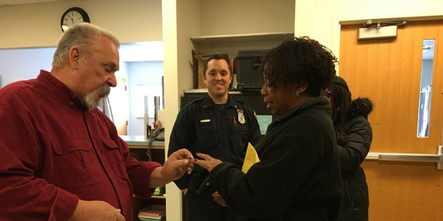 Milwaukee Police Officer Jason Schneider, center, and his father, left, helped a woman find her diamond wedding ring after she lost it in the snow last week.