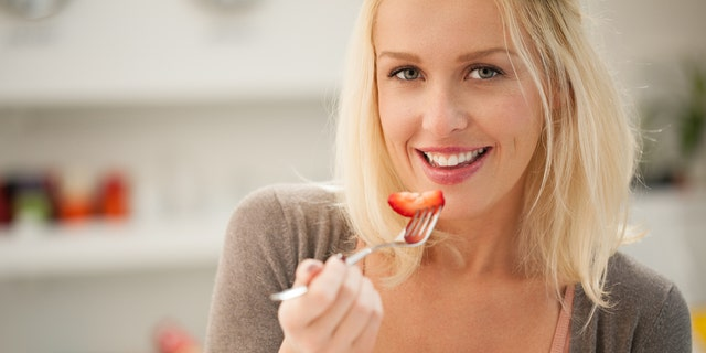 Smiling Caucasian woman eating a fresh fruit salad.