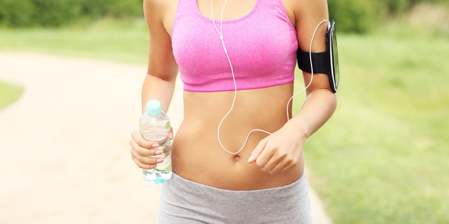 A picture of a woman jogging in the park with a bottle of water