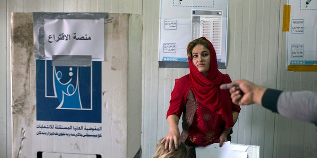 A volunteer points out the place where a displaced woman from Sinjar can cast her vote in the parliamentary elections, at a polling site in a camp for displaced people outside Irbil, Iraq, Saturday, May 12, 2018.