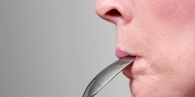 Woman eating the peanut butter off spoon