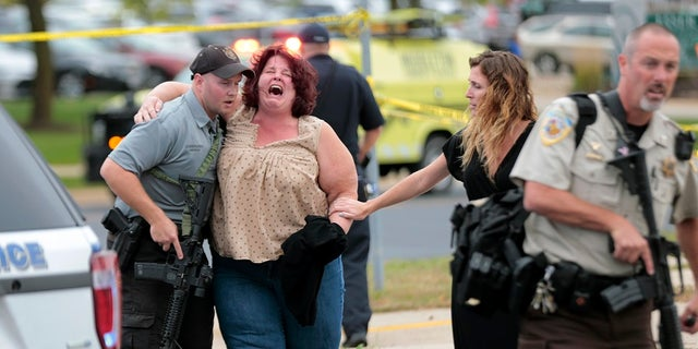 A women is escorted from the scene of a shooting at a software company in Middleton, Wis., Wednesday, Sept. 19, 2018.