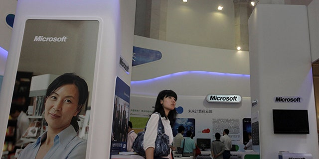 A visitor walks past a Microsoft booth at a computer software expo.