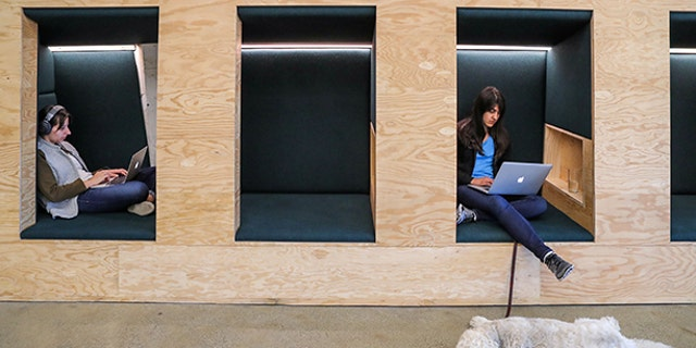 People work in cubes with their Apple computers at the Airbnb office headquarters in the SOMA district of San Francisco.