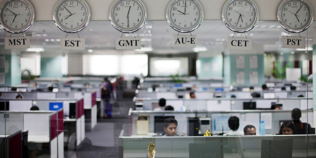 Workers are pictured beneath clocks displaying time zones in various parts of the world at an outsourcing center.