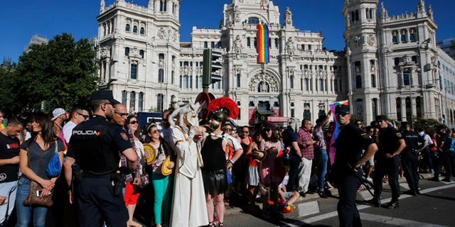 Participants and spectators mix in front of the City Hall with a rainbow flag hanging during the Gay Pride demonstration and parade, the climax of the 10-day WorldPride festivities, in Madrid, Spain, Saturday, July 1, 2017. Madrid is celebrating WorldPride 2017, a colorful mixture of vindication for sexual and gender diversity and all-night partying. (AP Photo/Paul White)