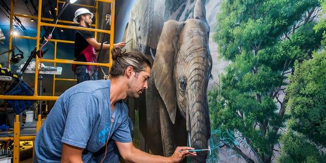 An artist hard at work on a mural.
