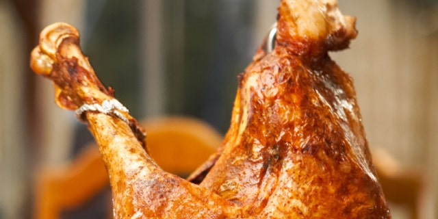 Fried turkey just after it has been fried resting in its frying stool