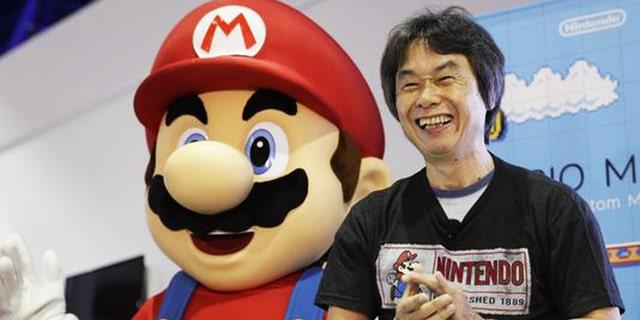 "Shigeru Miyamoto, the creator of ""Mario Bros."" and ""Donkey Kong,"" poses with a Super Mario character at a 2014 promotional event."